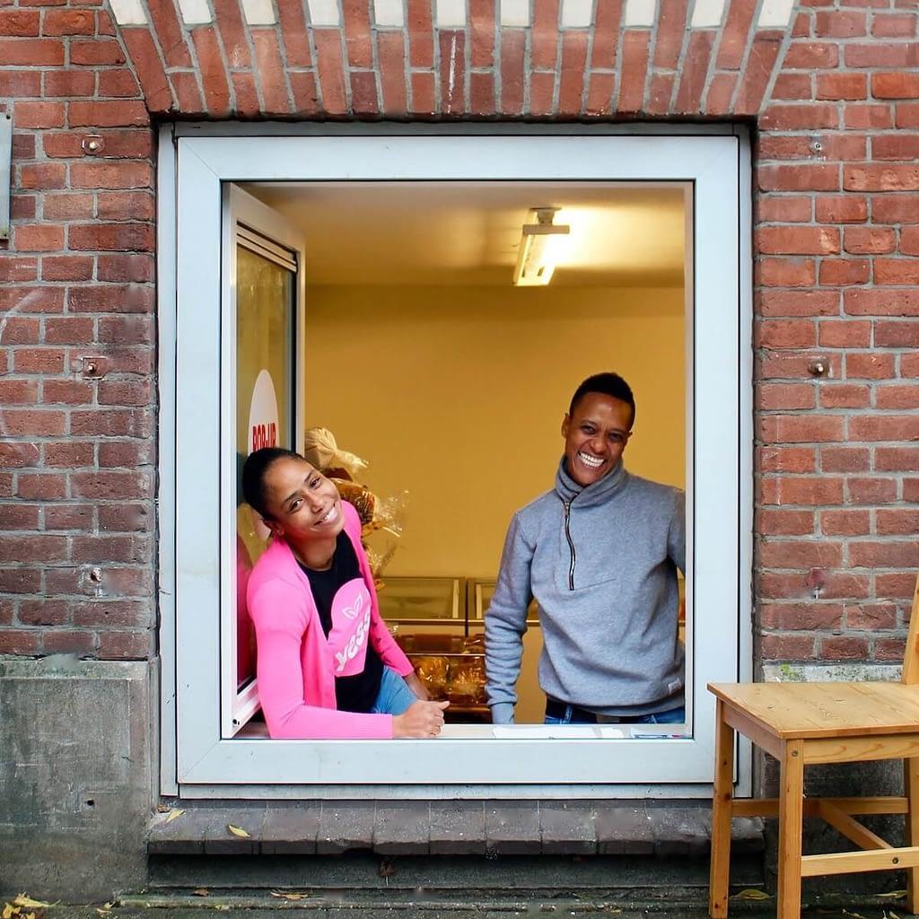Yess! De weggeefwinkel is geopend. Twee vrijwilligers staan bij het geopende raam klaar om mensen te ontvangen